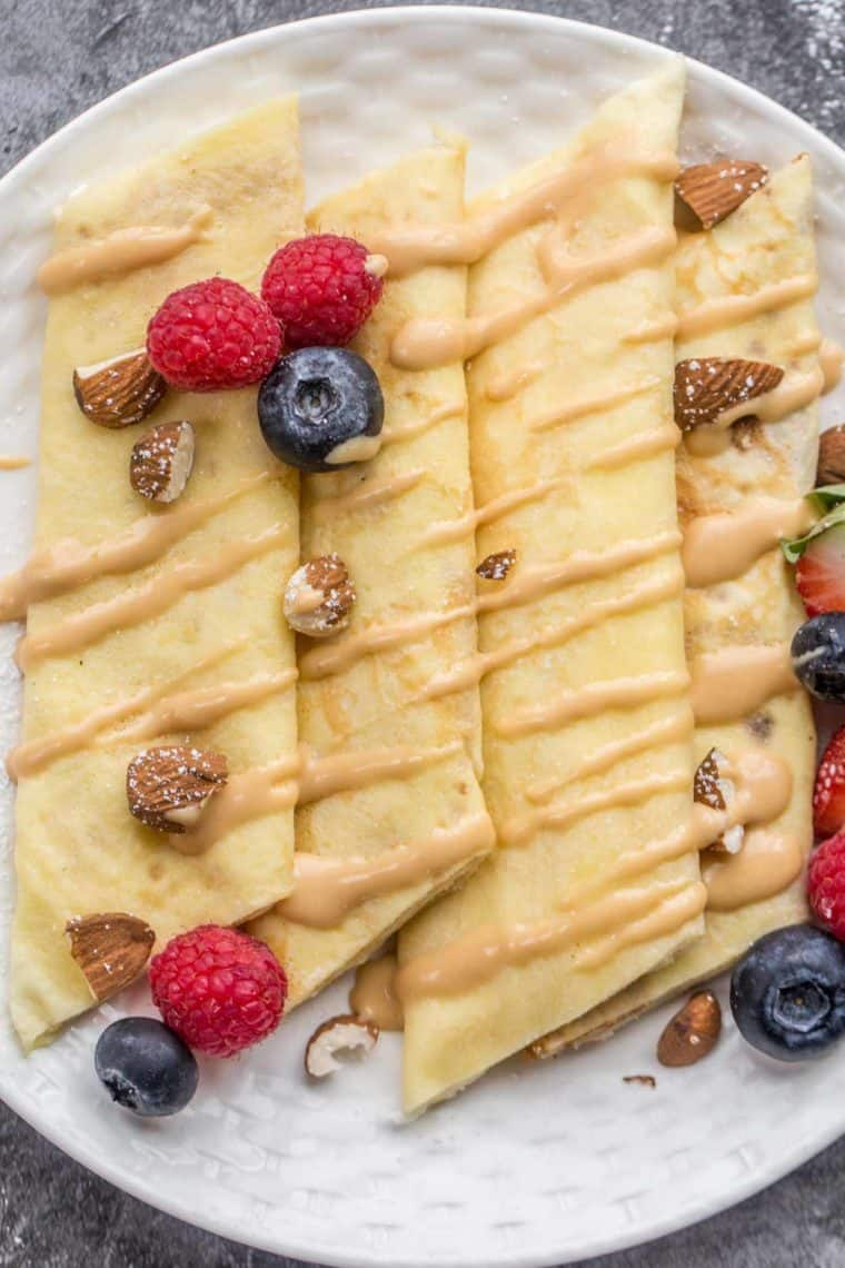 Homemade sweet crepes laid out on a plate topped with a caramel drizzle and fresh berries.