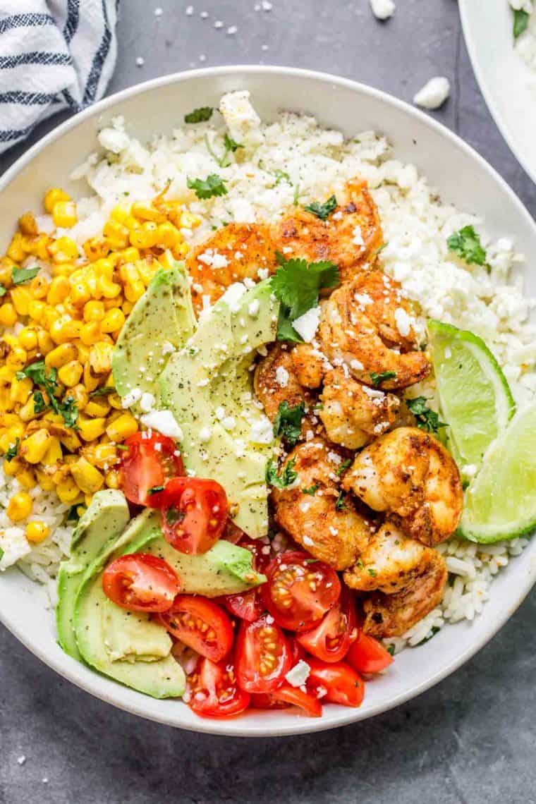 White bowl filled with rice, shrimp, corn, tomato, avocado, limes and feta cheese.