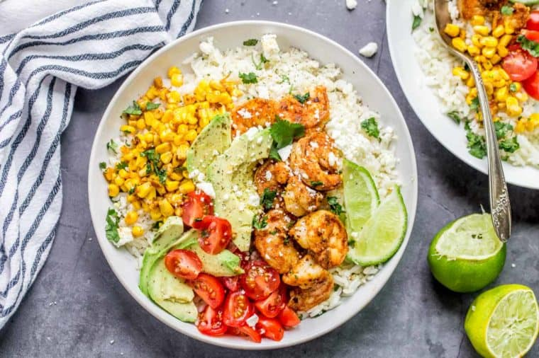 Shrimp rice bowl topped with freshly chopped greens next to another rice bowl and slices of lime and a striped cloth.