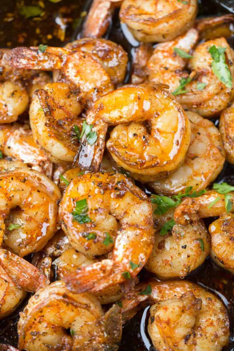 Garlic butter sautéed shrimp in a frying pan with black pepper and fresh greens.