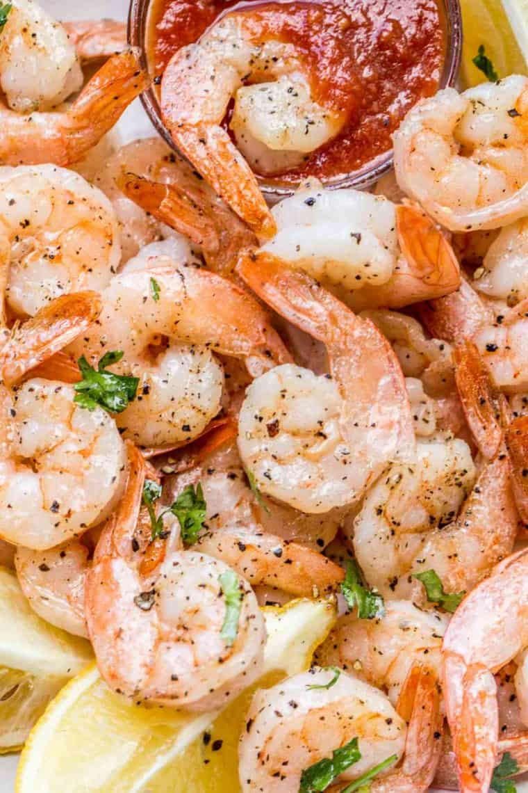 Baked shrimp in a bowl of cocktail sauce and lemon wedges garnished with green herbs.