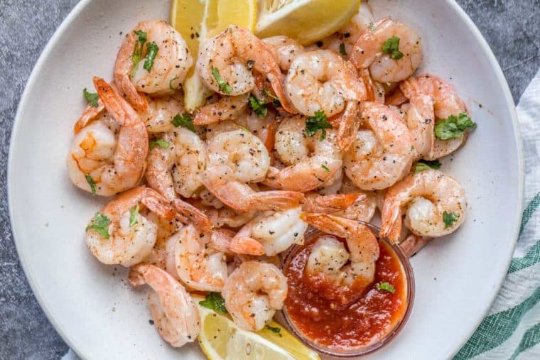 A white bowl filled with shrimp topped with pepper and fresh greens, with lemon slices and tartar sauce.