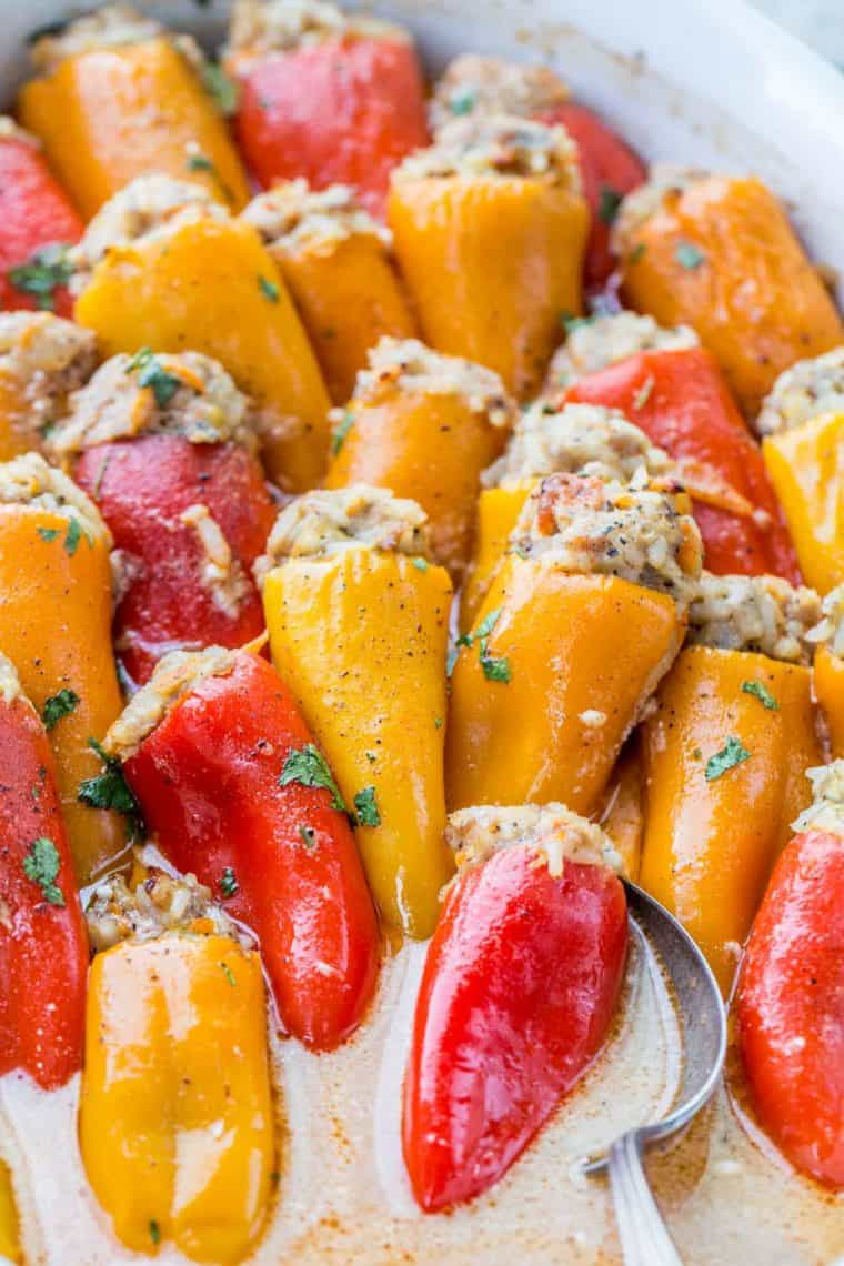 Stuffed mini bell peppers in a casserole dish topped with fresh chopped greens.