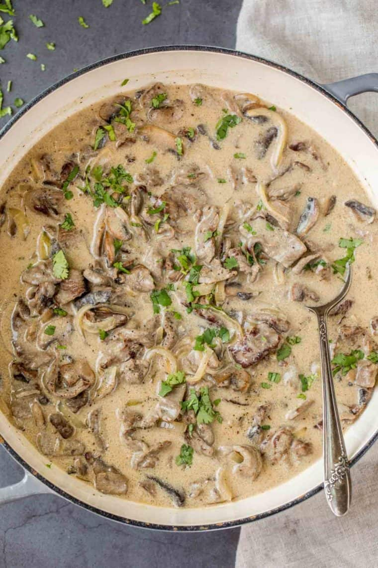 Beef stroganoff in a skillet loaded with mushrooms, onions and a creamy and rich sauce.