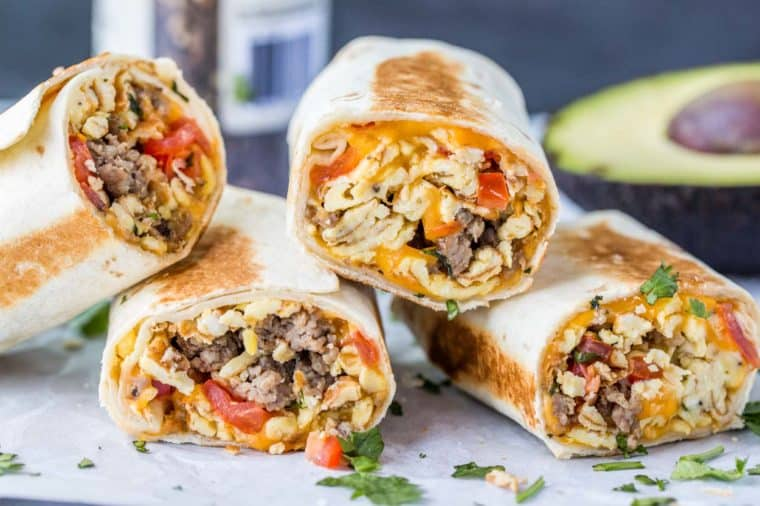 Breakfast burritos laid out next to each other and topped with chopped greens.