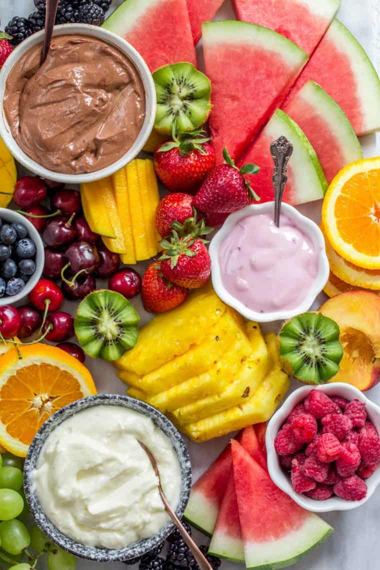 Fruit platter loaded with fruits and bowls of fruit dips.