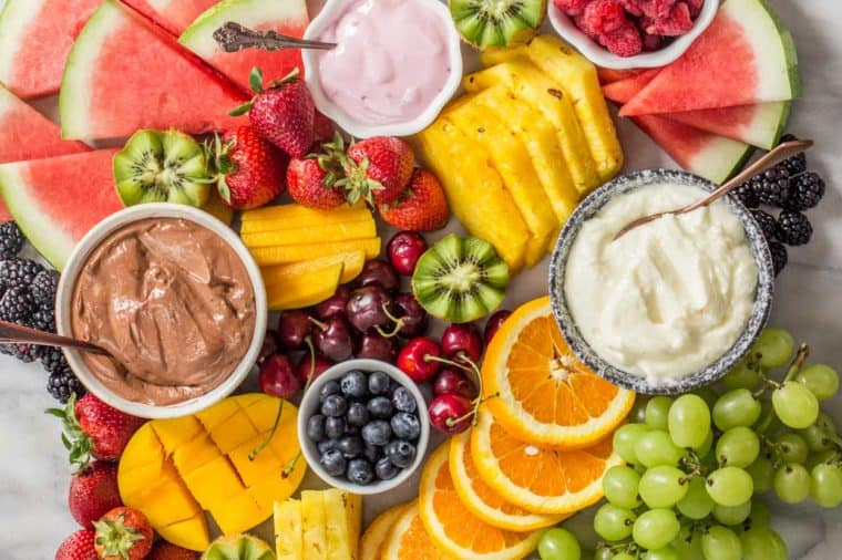 A fruit platter loaded with fruits, fruit dip, chocolate fruit dip and yogurt with spoons.