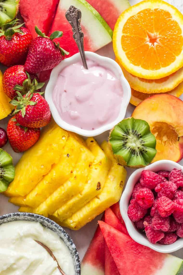 Sliced up fruit laid out on a board with a bowl or yogurt and a bowl or raspberries.
