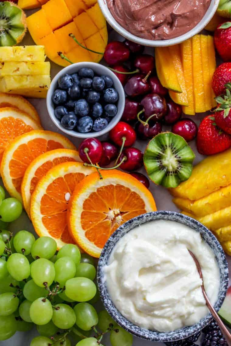 Berries, oranges, kiwi, and cherries laid out on a platter next to fruit dips.