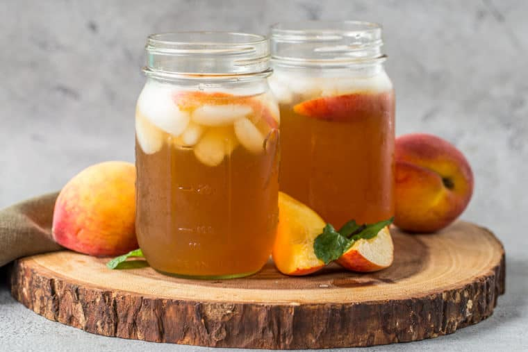 Jars of peach iced tea on a wooden board next to mint leaves and fresh slices of peaches.