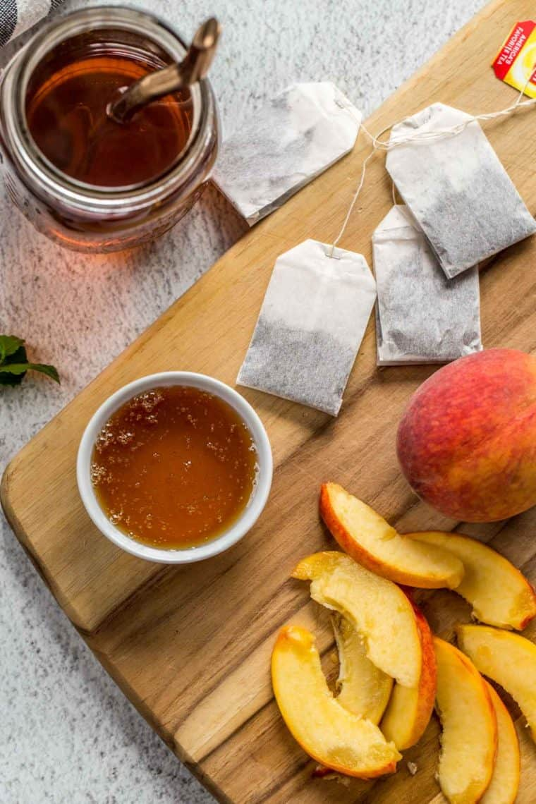 A glass of iced tea next to black tea bags, honey, and fresh peach slices.