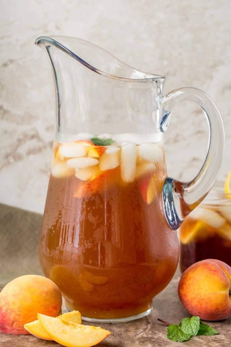 Peach tea in a glass pitcher next to fresh peaches and mint leaves.