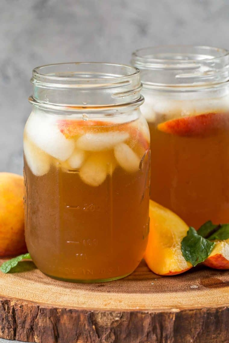 Two glass jars full of peach iced tea and ice on a wooden platter next to fresh peaches and mint leaves.