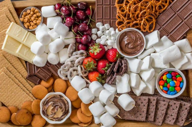 A smores dessert board loaded with fruits, chocolate, candy, crackers and marshmallows on a wooden tray.