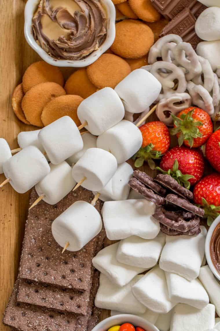 Marshmallows on skewers next to chocolate, graham crackers and fruits on a wooden tray.
