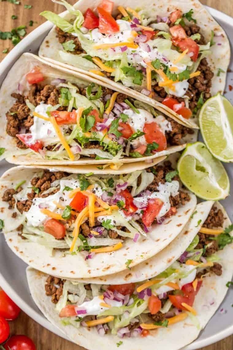 Four classic ground beef tacos on plate topped with shredded cheese, sour cream, tomatoes and fresh chopped greens.
