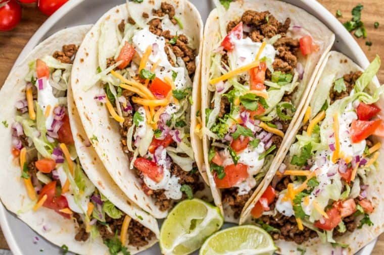 Flour tortillas loaded with ground beef meat and taco toppings.