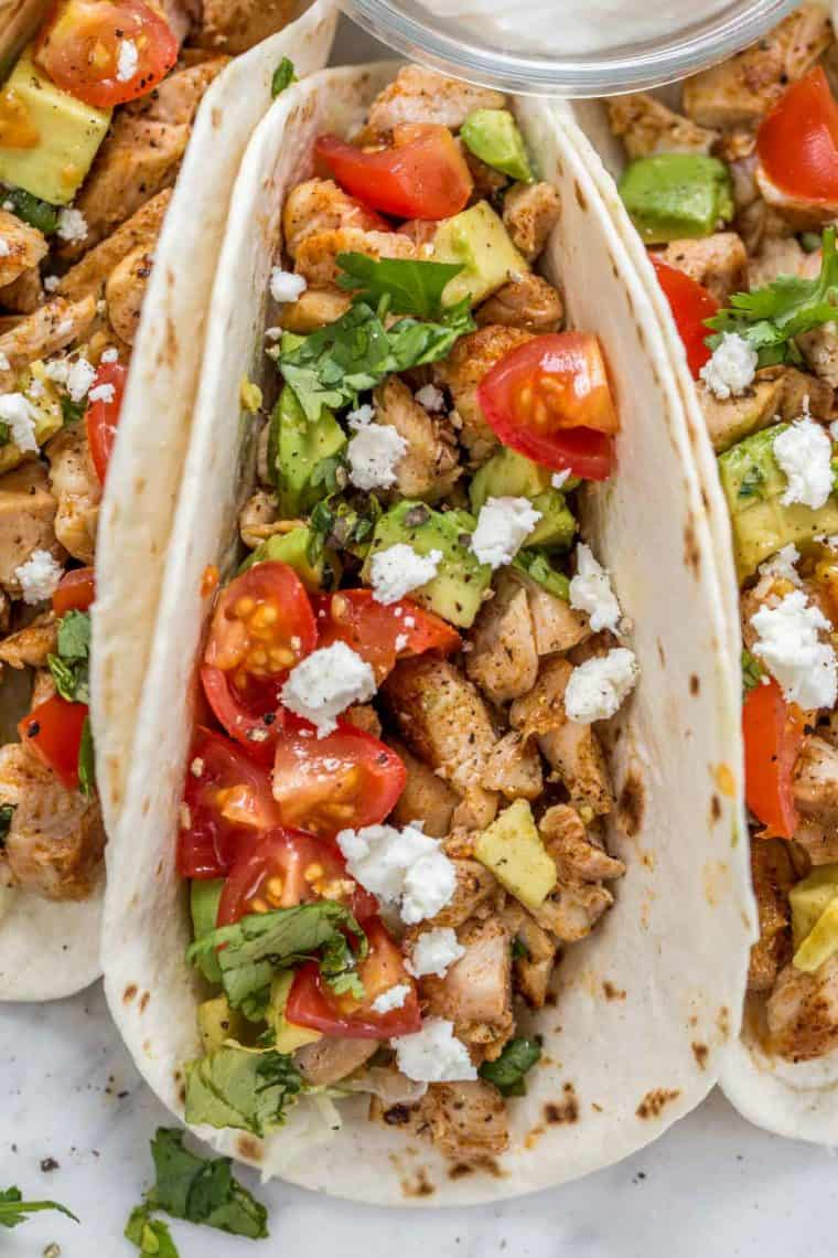 Flour tortilla loaded with season chicken, lettuce, tomatoes, avocado, Feta cheese, and fresh chopped greens.