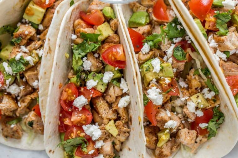 Four chicken tacos laid out on a plate topped with tomatoes, avocado, cheese and chopped greens.