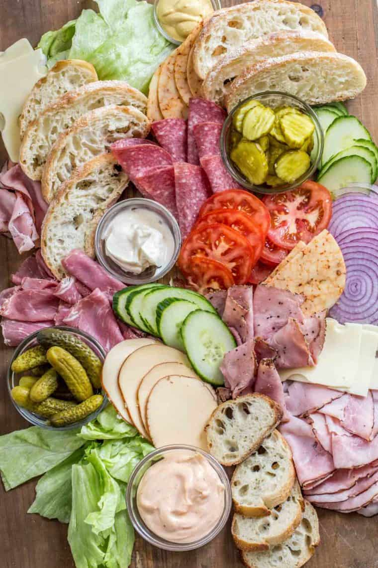 Lunch meats, cheese, bread, and toppings laid out on a wooden platter.