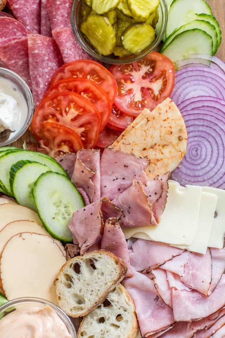 Tomato slices, cucumber slices, pickles, cheese, meat slices and bread all laid on a wooden platter.