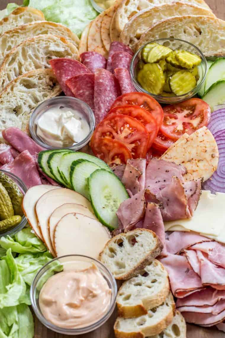 Cheese, bread, meat, and toppings laid out on a wooden platter with bowls of spread.