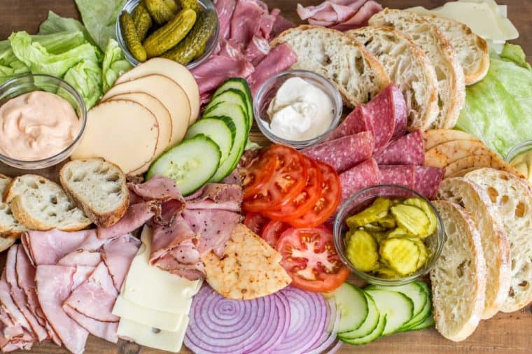 A wooden platter loaded with lettuce, cheese, tomatoes, onions, cucumbers, pickles, bread, and lunch meats.