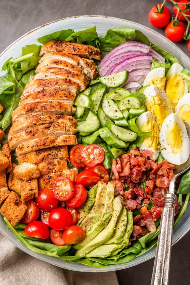 Spinach salad in a glass bowl loaded with cooked chicken, bacon, tomatoes, cucumbers and a metal spoon.