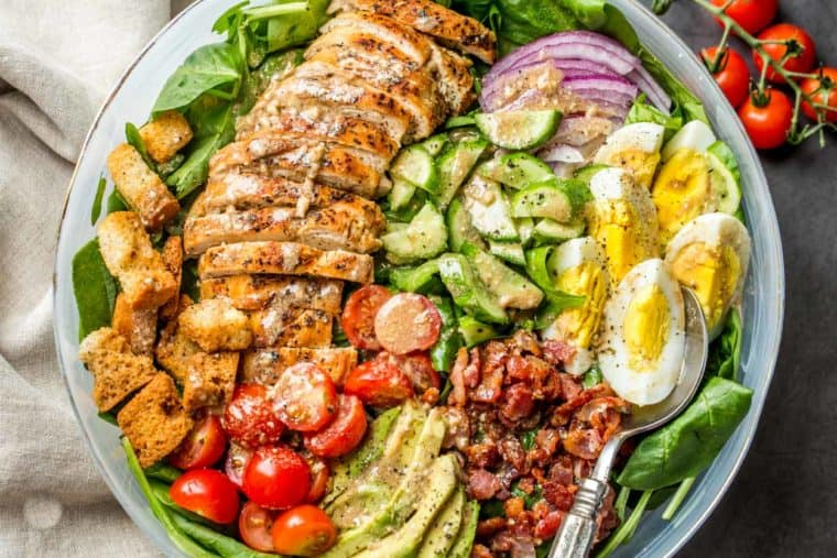 A white bowl loaded with spinach, croutons, chicken, tomatoes, cucumbers drizzled in a creamy dressing.