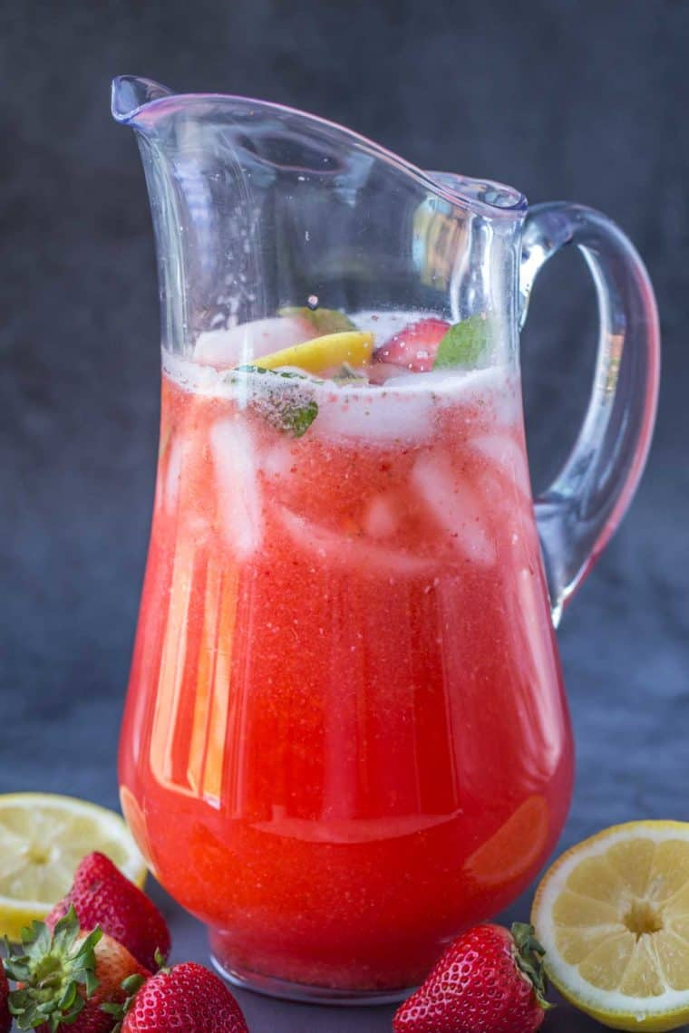 A pitcher with strawberry lemonade and ice with fresh strawberries and lemon slices on the sides of the pitcher.