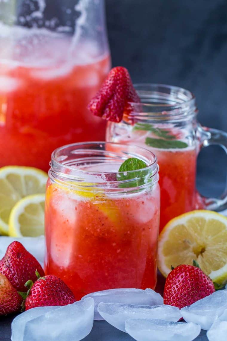 Two glass cups with strawberry lemonade and a pitchen of lemonade with fresh strawberries and lemon slices on the side and ice cubes.