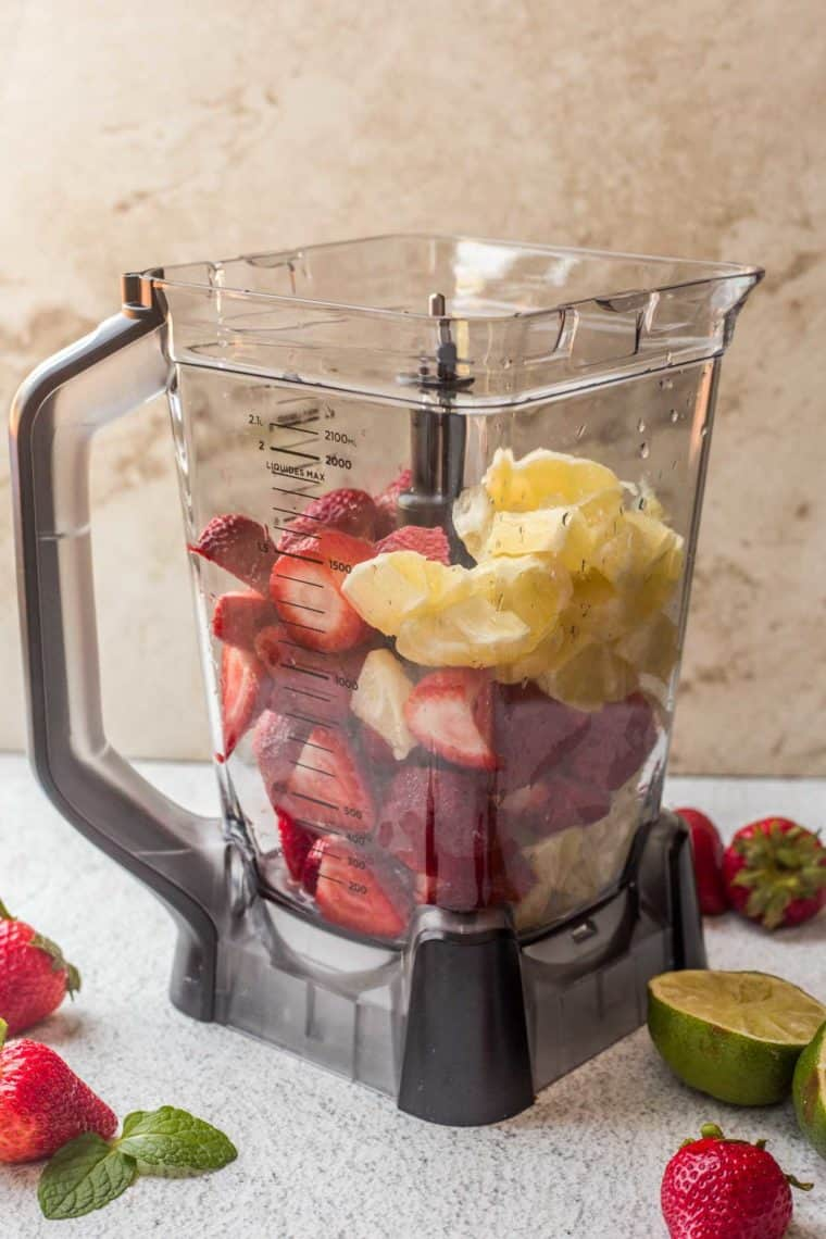 A blender filled with fresh strawberries and lemon with fresh strawberries and lime on the side of the blender.