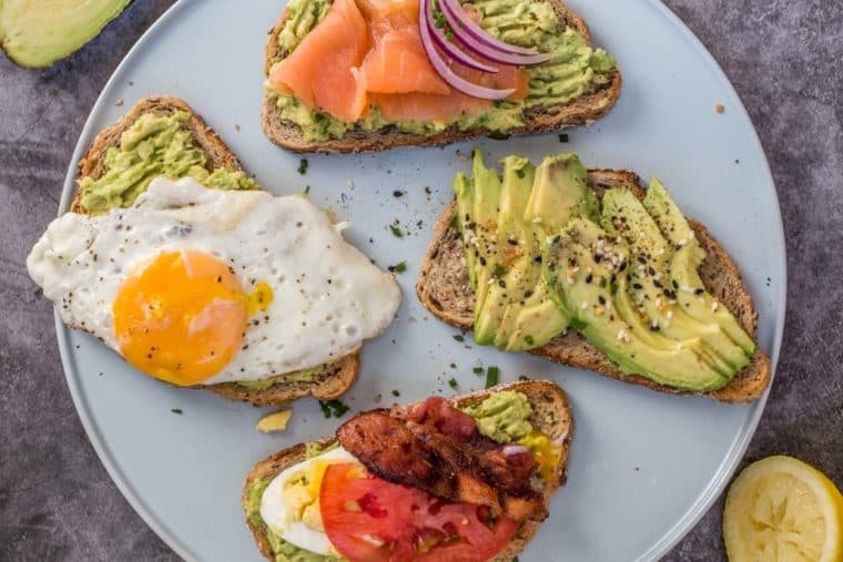 A blue plate with for avocado toast slices topped with egg, salmon, bacon, and tomatoes.