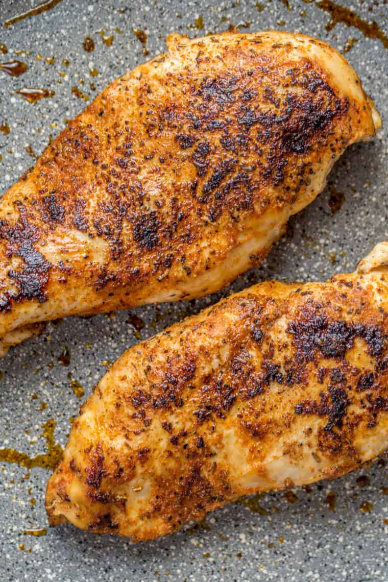 Two pan seared chicken breasts in a gray skillet.