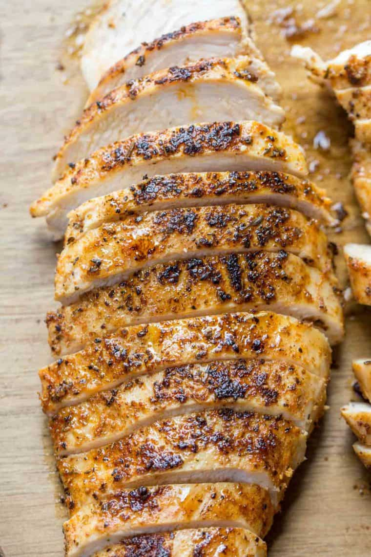 Pan seared chicken breast sliced into thin pieces on a cutting board.