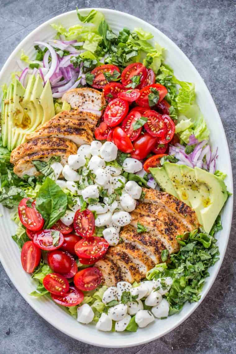 A white serving bowl loaded with romaine, tomatoes, onions, avocados, chicken, and mozzarella cheese.