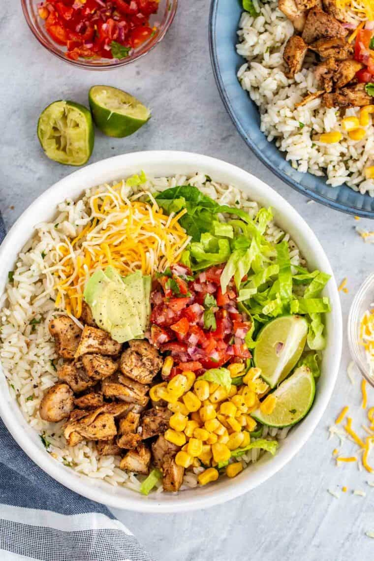 Chicken chipotle bowl next to another chipotle bowl with limes and cheese.