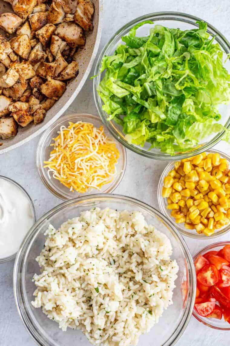 All the ingredients needed for homemade chipotle bowls in glass bowls.