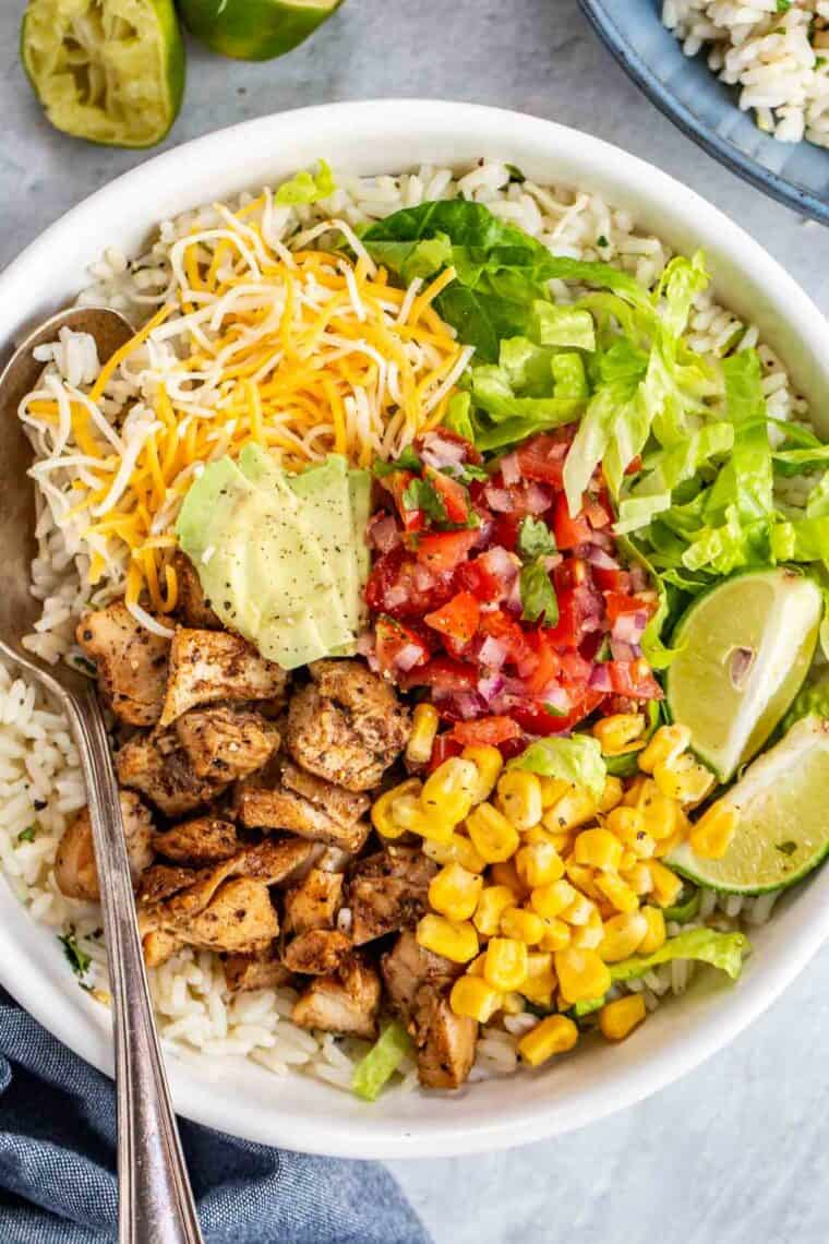 White rice, chicken, corn, lettuce, tomato, cheese and avocado loaded in a white bowl.
