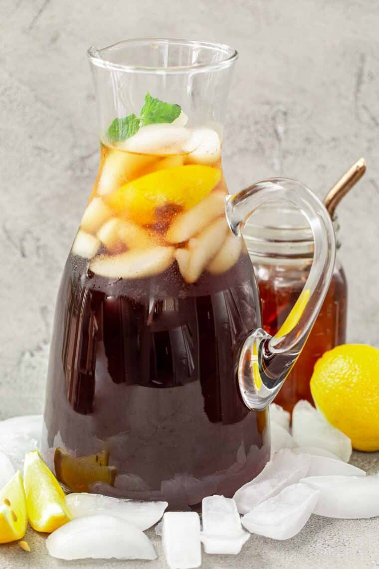 Homemade sweet tea in a pitcher next to ice, lemon and lemon slices.
