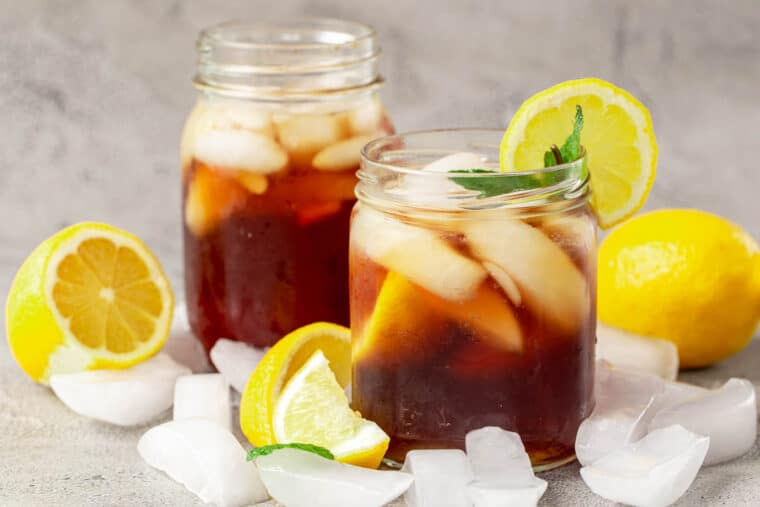 Two cups of homemade iced tea next to lemons and ice.