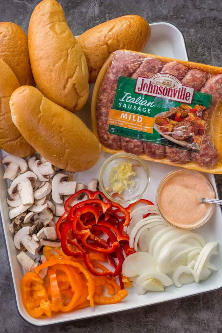 Italian sausages, prepped vegetables and hoagies on a tray ready for grilling.