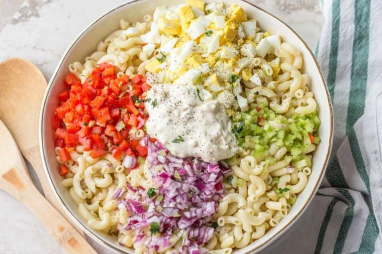 A white bowl loaded with macaroni salad ingredients laid out next to wooden spoons and a green and white rag.