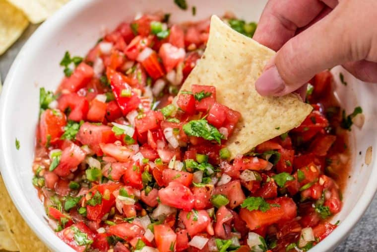 Pico de gallo in a white bowl with a chip being dipped in the salsa.
