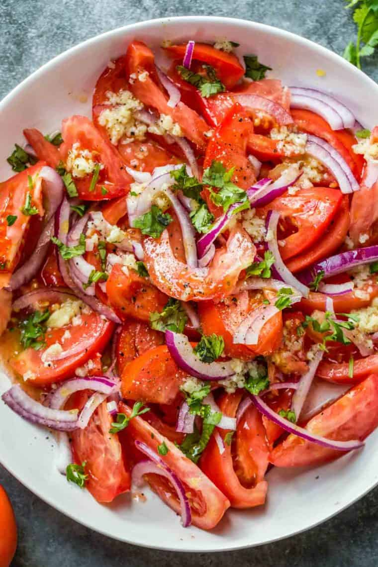 A white bowl loaded with tomatoes salad topped with fresh chopped greens.