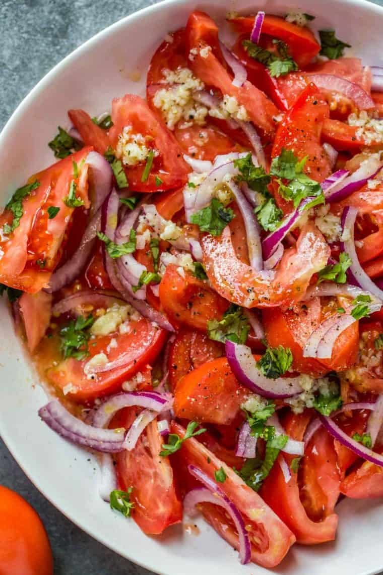 Tomato salad in a white bowl topped with fresh chopped greens next to a tomato.