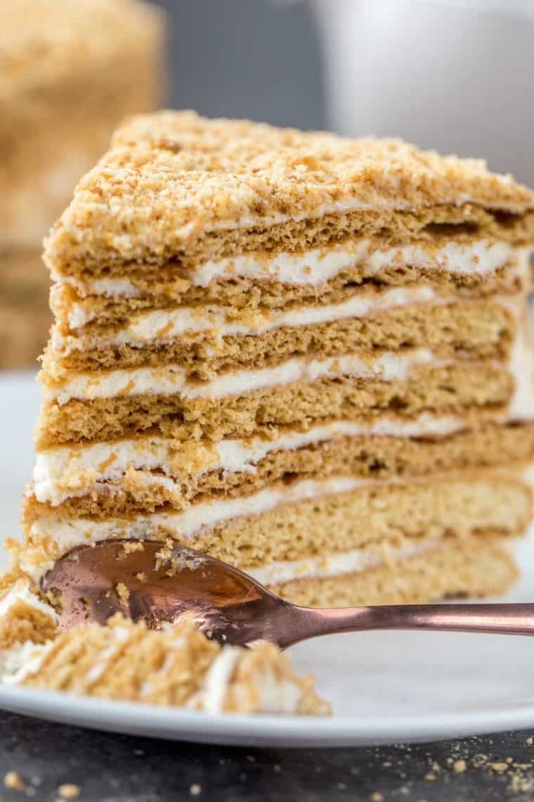 A slice of honey cake on a plate with a spoonful full of cake next to the cake slice.