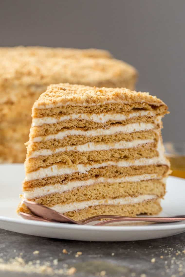 A slice of homemade honey cake on a white plate with a golden spoon next to the cake slice.