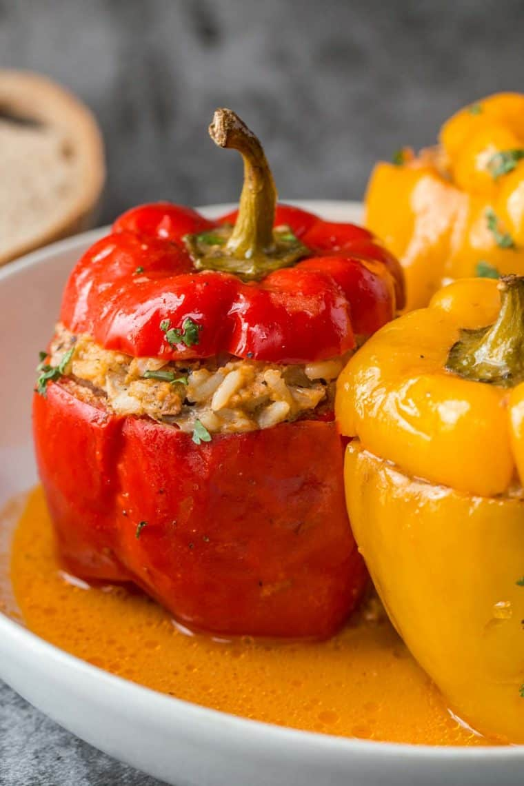 Stuffed peppers topped with fresh chopped greens on a plate.