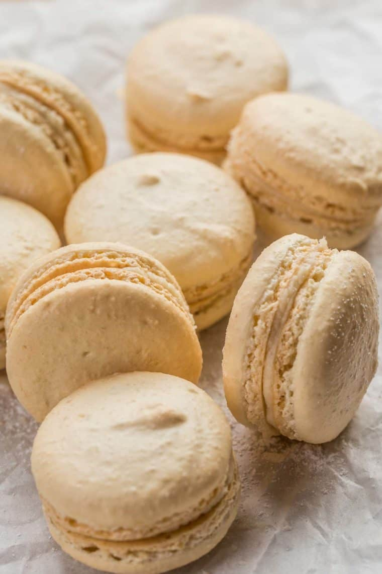 Classic French macarons laid out on a parchment paper topped with powdered sugar.